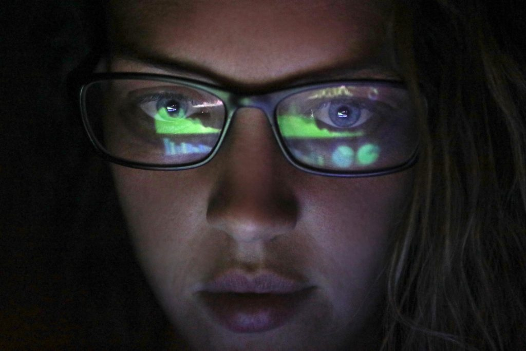 female looking at screen in dark